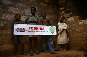 Children holding Toshiba and c02balance advertisement regarding their massive environmental help in that region.