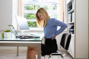 Side View Of A Young Businesswoman Suffering From Back Pain In Office